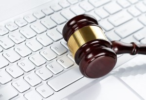 Close up of wooden gavel at the computer keyboard