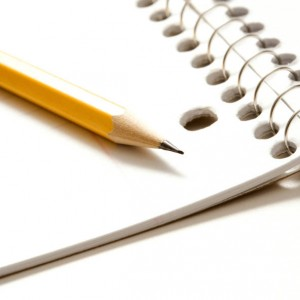 Sharp pencil placed on open spiral bound notebook.
