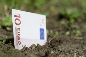 Banknote of ten euro coming up from the ground